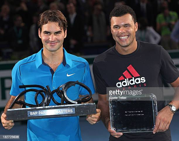 Winner Roger Federer of Switzerland and runnerup JoWilfried Tsonga of France hold their respective trophies after their final match in the BNP...