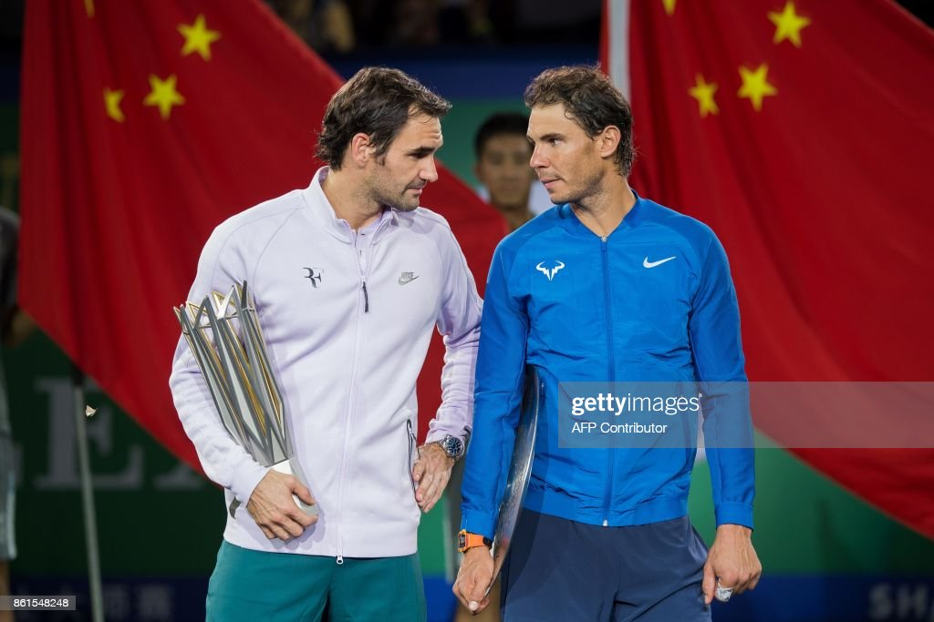 Winner Roger Federer of Switzerland (L) and second-placed Rafael Nadal of Spain hold their trophies after the men's singles final match at the Shanghai Masters tennis tournament in Shanghai on October 15, 2017. / AFP PHOTO / Nicolas ASFOURI