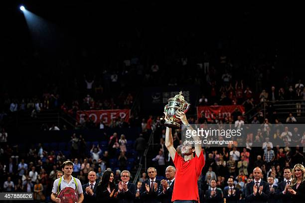 Winner Roger Federer of Switzerland lifts the trophy as runnerup David Goffin of Belgium looks on after the Swiss Indoors ATP 500 tennis tournament...