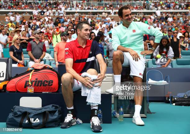 Winner Roger Federer of Switzerland sits with runner up John Isner of USA after the final during day fourteen of the Miami Open tennis on March 31,...