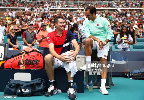 Winner Roger Federer of Switzerland sits with runner up John Isner of USA after the final during day fourteen of the Miami Open tennis on March 31...