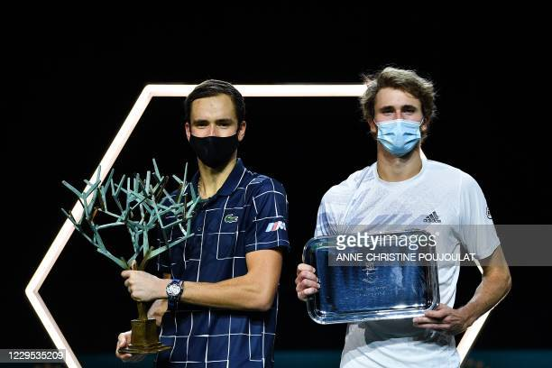 Winner Russia's Daniil Medvedev and second-placed Germany's Alexander Zverev pose with their trophies after competing in the men's singles final...
