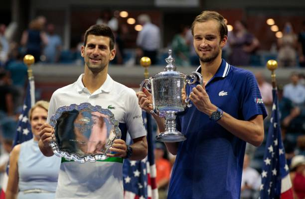 Winner Russia's Daniil Medvedev and Serbia's Novak Djokovic hold their trophies after the 2021 US Open Tennis tournament men's final match against at...