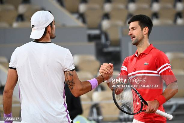 Winner Serbia's Novak Djokovic congratulates Italy's Matteo Berrettini at the end of their men's singles quarter-final tennis match on Day 11 of The...