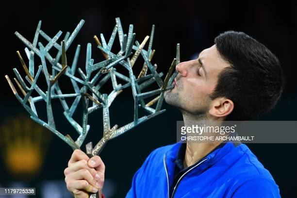Winner Serbia's Novak Djokovic kisses his trophy after winning against by Canada's Denis Shapovalov during their men's singles final tennis match at...