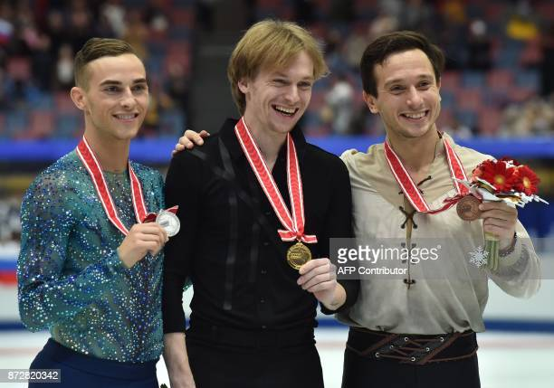Winner Sergei Voronov of Russia poses with secondplace Adam Rippon of the US and thirdplace Alexei Bychenko of Israel during the award ceremony of...