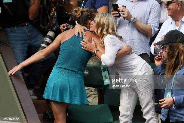 Winner Simona Halep of Romania is greeted by Nadia Comaneci in the stands after winning the French Open final on Day 14 of the 2018 French Open at...