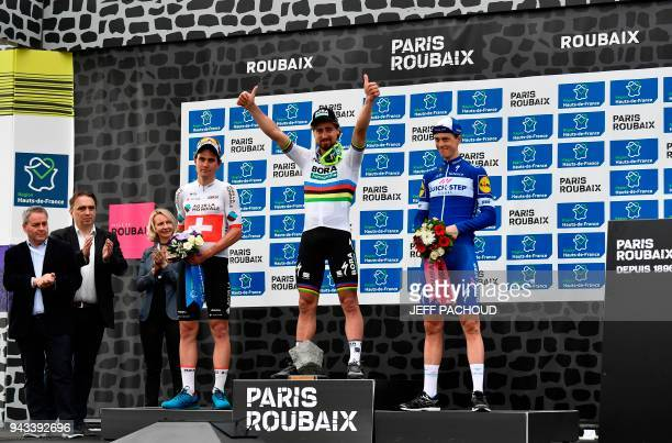 Winner Slovakia's Peter Sagan celebrates on the podium next to secondplaced Switzerland's Silvan Dillier and South Africa's Jaco Venter after the...