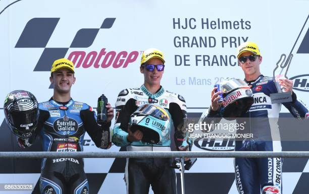 Winner Spain's rider Joan Mir celebrates with second placed Spain's Aron Canet and third placed Italy's rider Fabio Di Giannantonio on the podium...