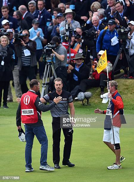 Winner Sweden's Henrik Stenson is congratulated by Phil Mickelson's caddie Jim McKay on the 18th green after his final round shooting 63 in his final...