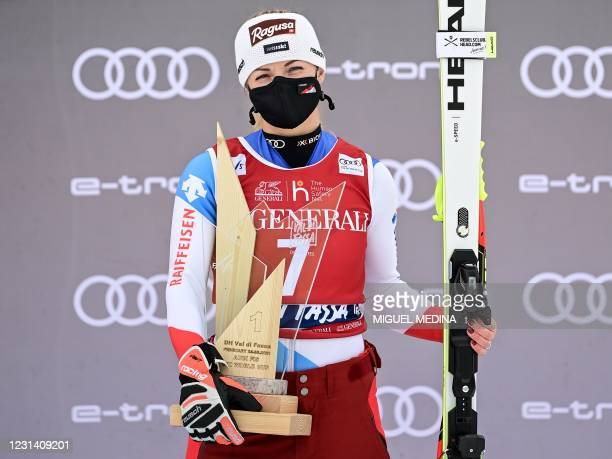 Winner Switzerland's Lara Gut-Behrami celebrates her victory on the podium with her trophy after the FIS Alpine Ski Women's World Cup downhill, in...