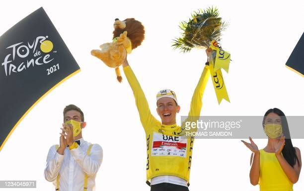 Winner Team UAE Emirates' Tadej Pogacar of Slovenia celebrates his overall leader yellow jersey on the podium at the end of the 21th and last stage...