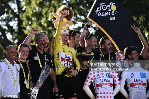 Winner Team UAE Emirates' Tadej Pogacar of Slovenia celebrates wearing the overall leader yellow jersey celebrates with his team staff members on the...