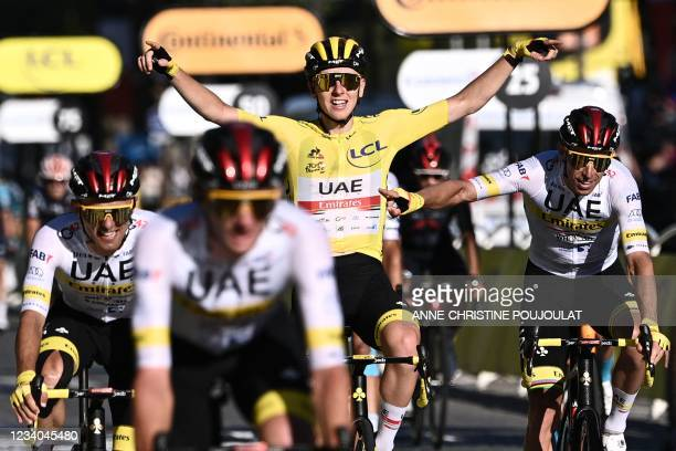 Winner team UAE Emirates' Tadej Pogacar of Slovenia wearing the overall leader's yellow jersey celebrates with his teammates as he crosses the finish...