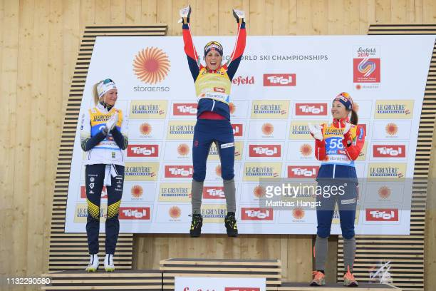 Winner Therese Johaug of Norway celebrates on the podium with second placed Frida Karlsson of Sweden and third placed Ingvild Flugstad Oestberg of...