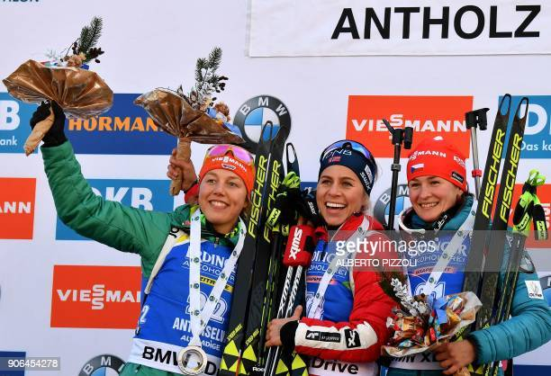 Winner Tiril Eckhoff of Norway celebrates on the podium next to second placed Laura Dahlmeier of Germany and third placed Veronika Vitkova of Czech...