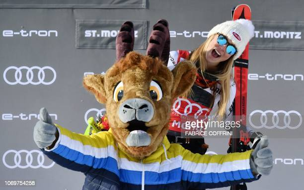 Winner US Mikaela Shiffrin celebrates with the mascot on the podium after competing in the Women's Super G race during the FIS Alpine Ski World Cup...