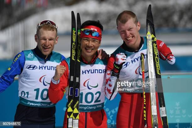 Winner Yoshihiro Nitta of Japan celebrates with Silver medallist Grygorii Vovchynskyi of Ukraine and Bronze medallist Mark Arendz of Canada during...