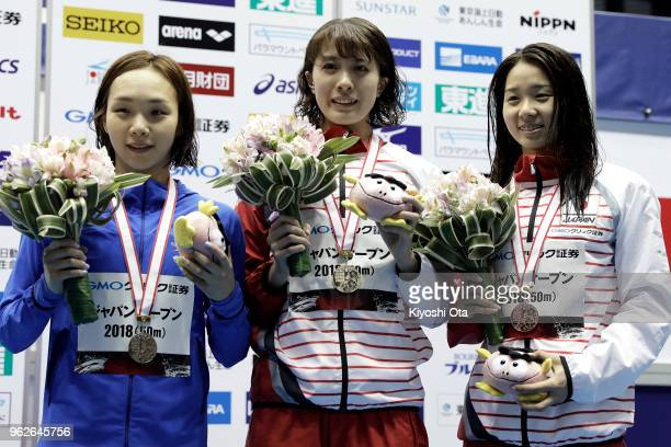 Winner Yui Ohashi of Japan celebrates with runnerup Kim Seoyeong of South Korea and thirdplaced Miho Teramura of Japan after the Women's 200m...