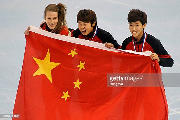 WinnerMeng Wang of China and 2nd PlaceKexin Fan of China hold national flag with the 3rd PlaceMarianne Stgelais of Canada at ceremony of the Women's...