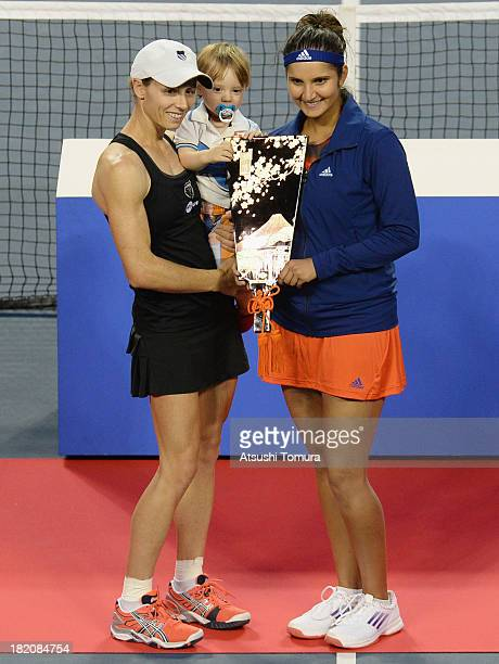 Winners Cara Black of Zimbabwe and Sania Mirza of India celebrate with their plate after the match against HaoChing Chan of Chinese Taipei and Liezel...
