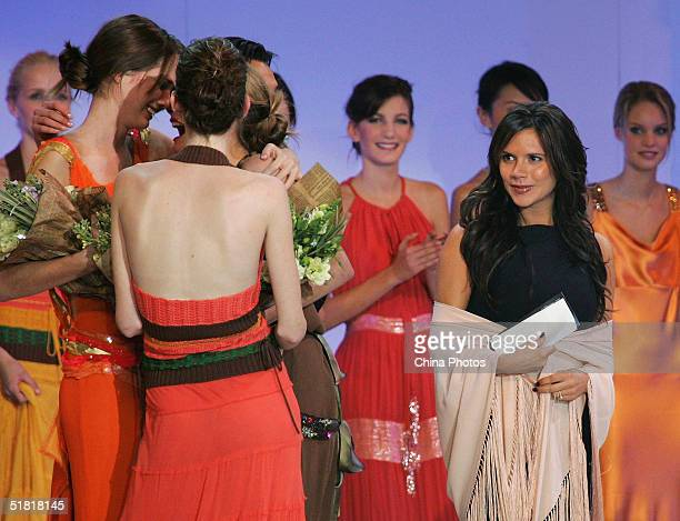 Winners celebrate with each other as Victoria Beckham looks at during the OLAY Elite Model Look 2004 International Finals on December 2 2004 in...