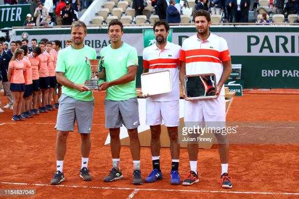 Winners Kevin Krawietz of Germany and partner Andreas Mies of Germany stand next to runners up Jeremy Chardy of France and Fabrice Martin of France...
