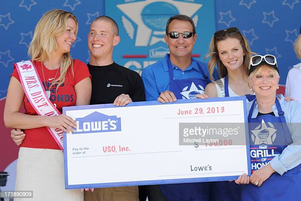 Winners Lance Corporal Noah Bratcher and his wife Cassandra Bratcher pose with Tom Lamb of Lowes Brooklyn Decker and Elaine Rodgers of USO during...