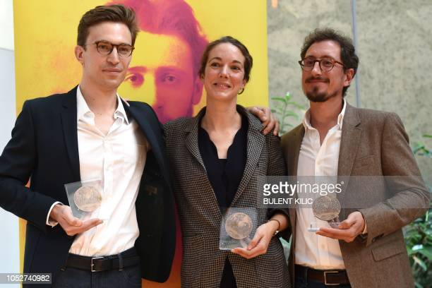 Winners of the Albert Londres prize French journalists Elise Vincent JeanBaptiste Malet and Christophe Barreyre pose with their trophy during the...