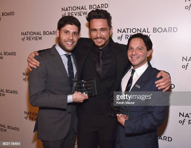 Winners of the Best Adapted Screenplay Award for The Disaster Artist Michael Weber and Scott Neustadter pose with presenter and actor James Franco...