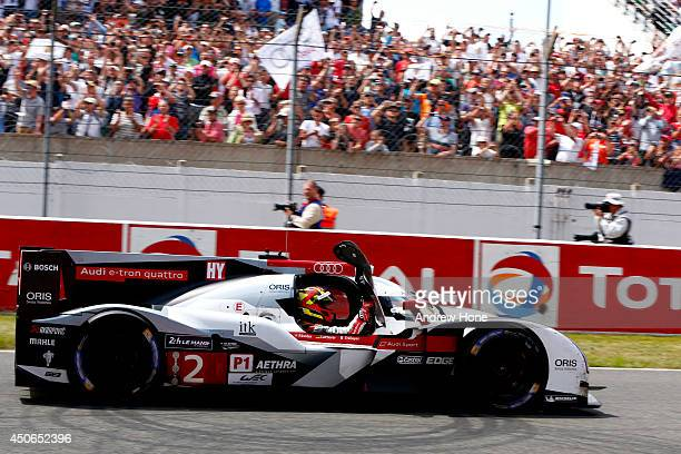 Winners of the Le Mans 24 Hour 2014 Audi Sport Team Joest Audi R18 ETron Quattro of Marcel Fassler André Lotterer and Benoit Treluyer cross the line...