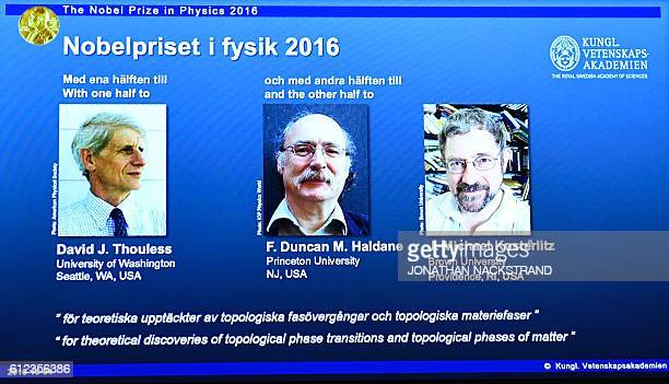 Winners of the Nobel Prize in Physics David J Thouless F Duncan M Haldane and J Michael Kosterlitz are displayed on a screen during a press...