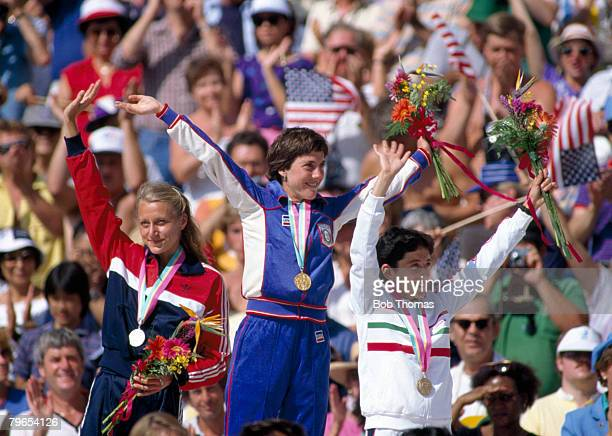 Winners of the Women's Marathon event stand together and wave on the podium with from left to right silver medal winner Grete Waitz of Norway gold...