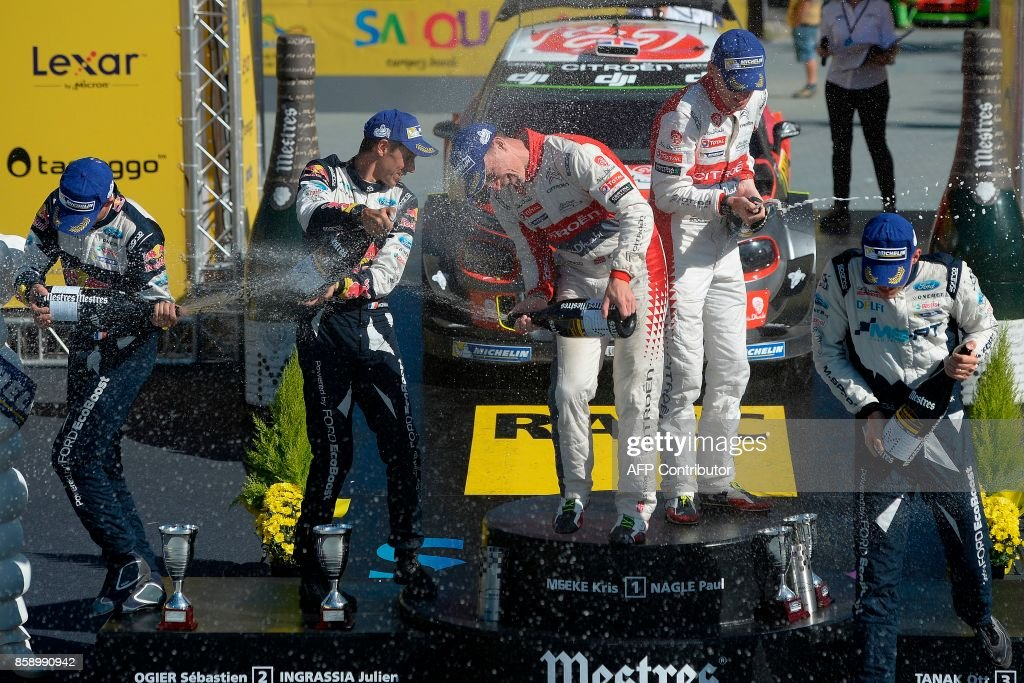 Winners Paul Nagle of Ireland (4L) and British Kris Meeke (3L), second placed French drivers Sebastien Ogier (L) and his co-driver Julien Ingrassia (2L) and third place Ott Tanak of Estonia (R) sprays cava on the podium of the 53th Rally of Catalonia in Salou near Tarragona on October 8, 2017. Britain's Kris Meeke bagged his second win of the season at the Rally of Catalonia as France's Sebastian Ogier took a big step towards a fifth straight world title. / AFP PHOTO / Josep LAGO