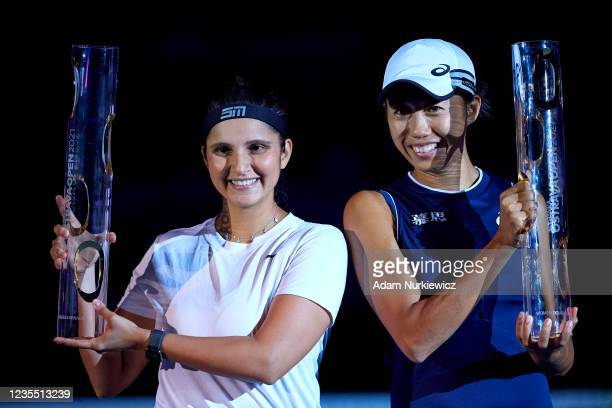 Winners Sania Mirza of India and Shuai Zhang of China pose with their trophies during the awarding ceremony following the Doubles Final on Day 7 of...