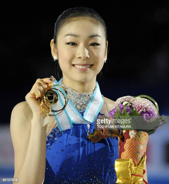 Winnes of the ladies' singles free skating competition, Kim Yu-Na of South Korea holds up her gold medal on the podium of the figure skating ISU...