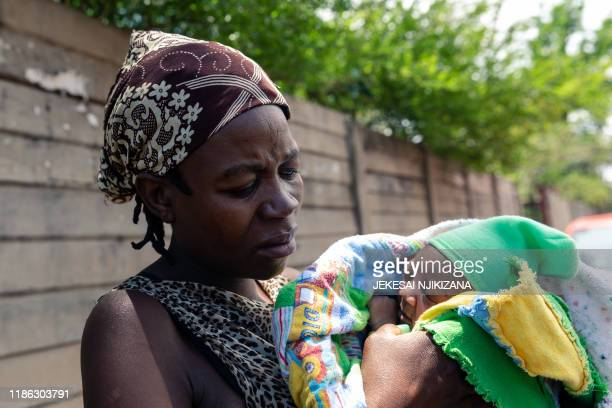 Winnie Denhere cradling her twodayold baby boy delivered by Esther Gwena outside Edith Opperman clinic where the baby is to receive a BCG vaccine...