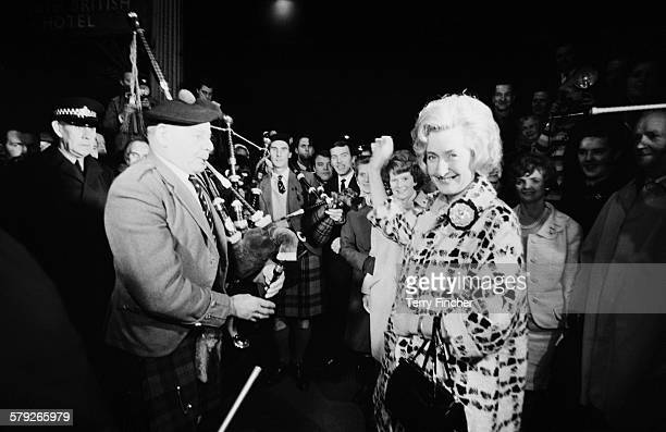 Winnie Ewing the newlyelected Scottish National Party Member of Parliament for Hamilton is welcomed by supporters including two highland bagpipers as...