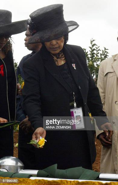 Winnie MadikizelaMandela the former wife of former South African president Nelson Mandela tosses a rose on the grave of Makgatho son of Neslon...