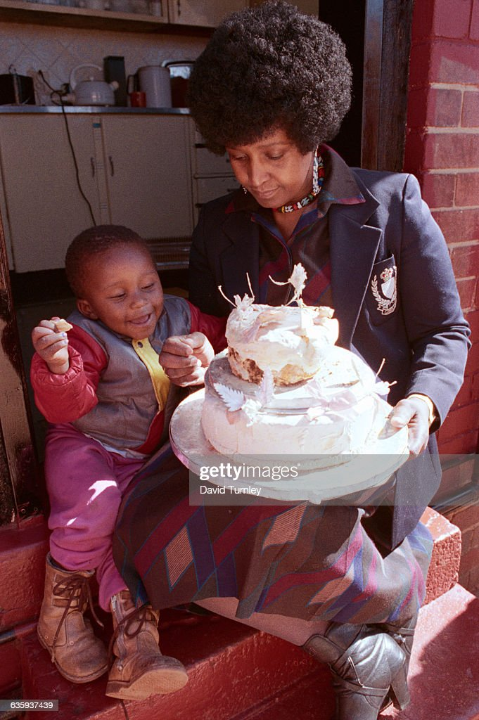 Winnie Mandela shows part of her wedding cake to her grandson. The wife of jailed anti-apartheid activist Nelson Mandela, she has saved the cake for more than two decades.