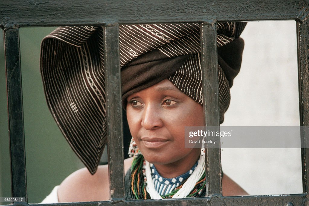 Winnie Mandela, the wife of political prisoner Nelson Mandela, looks out from behind the barred gate at her home, where she lived in defiance of a 1985 government order banishing her to the Orange Free State.