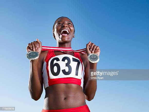 winning athlete with two medals around neck - medallist stock pictures, royalty-free photos & images