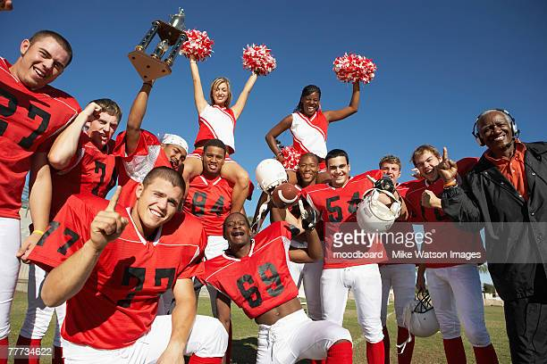 Winning Football Players with Coach and Cheerleaders