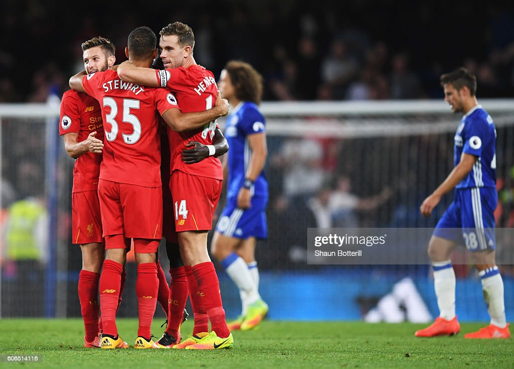 Winning goalscorer Jordan Henderson of Liverpool (14) celebrates victory with Adam Lallana (L) and Kevin Stewart after the Premier League match between Chelsea and Liverpool at Stamford Bridge on September 16, 2016 in London, England.
