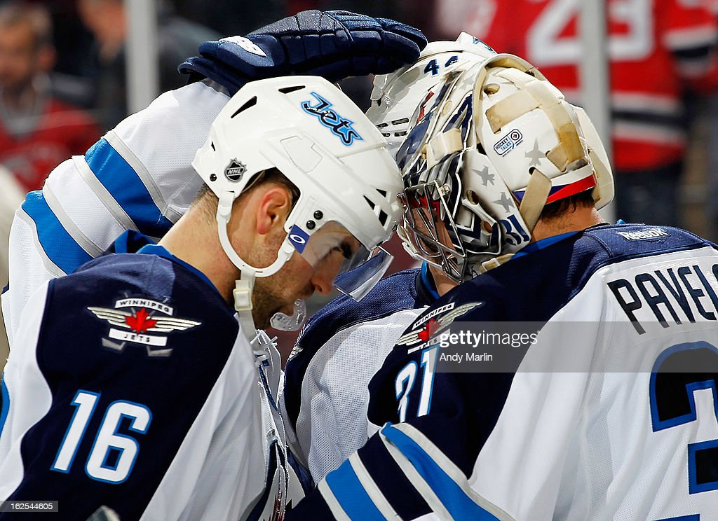 Winning goaltender Ondrej Pavelec #31 of the Winnipeg Jets is congratulated by Andrew Ladd #16 after defeating the the New Jersey Devils at the Prudential Center on February 24, 2013 in Newark, New Jersey. The Jets defeated the Devils 4-2.