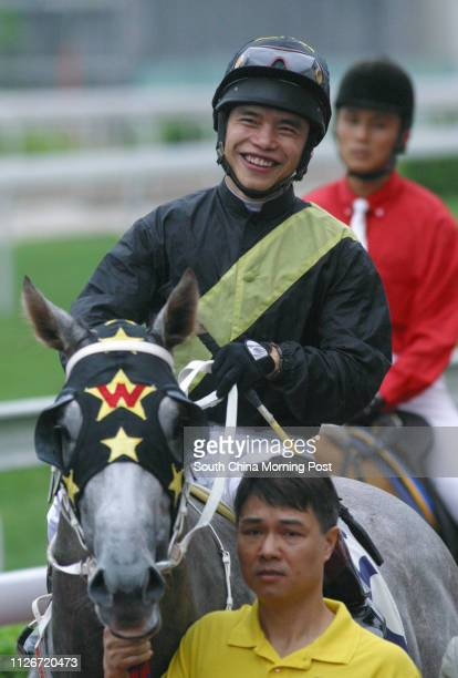 Winning horse Flying Kenny and jockey Simon Yim are led back after winning the Race 1 at Sha Tin Racecourse 18 May 2003