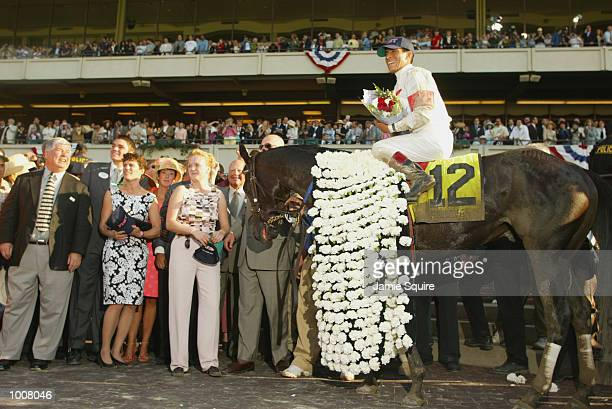 Winning horse Sarava wears his blanket of white carnations and jockey Edgar Prado smiles in the winners' circle at the 134th Belmont Stakes at...