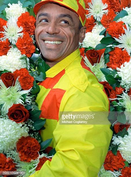 Winning jockey holding floral arrangement, portrait