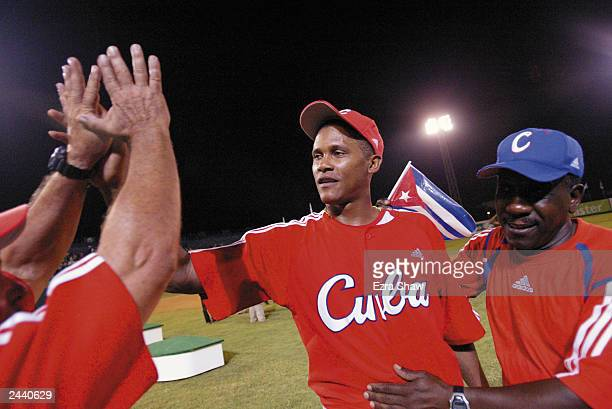 Winning pitcher Norge Luis Vera of Cuba is congratulated after they defeated the USA during Men's Baseball at Quisqueya Stadium on August 12 2003 at...