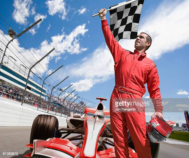 Winning race car driver standing in front of car.